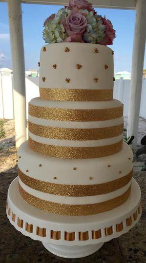 Three tier white and gold wedding cake
