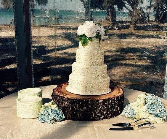 Four tier white wedding cake with flowers on top