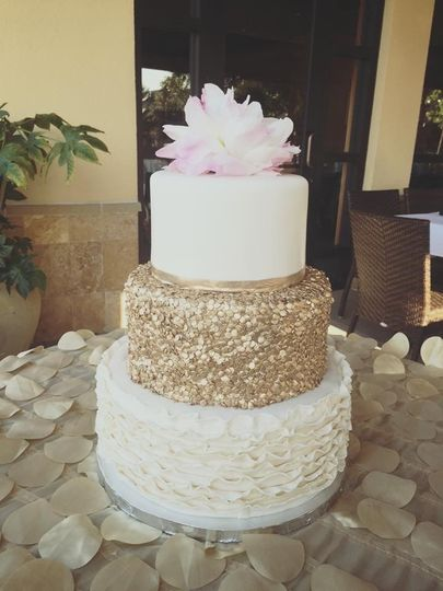 Three tier gold and white cake with flower on top