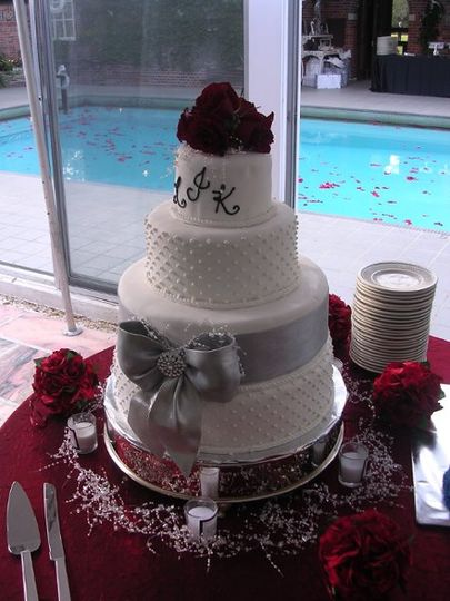 Four-layered fondant cake with accenting silver bow and crystal center, red roses with pipped...
