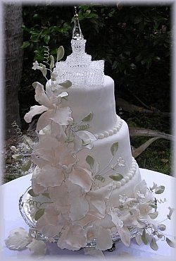 Three layered fondant cake with hand-made edible orchids luster-dusted to the brides colors....
