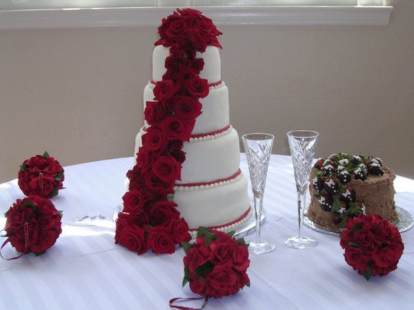 This four layered cake is adorned with fresh red roses cascading down the fondant icing.  The grooms...