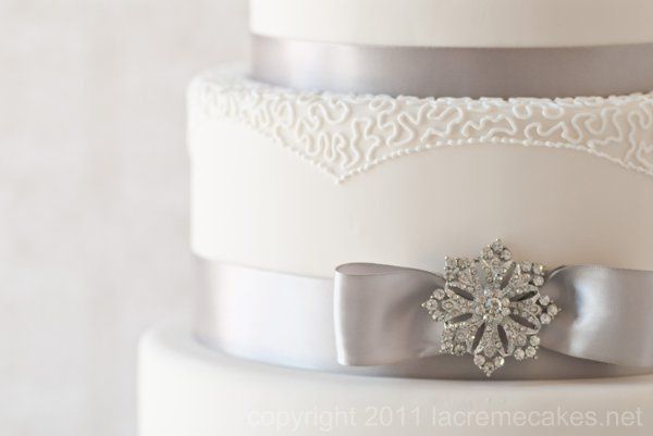 Piped lace detail and antique style brooches add elegance to this silver and white wedding cake