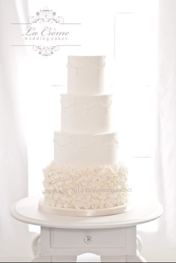 A soft romantic wedding cake with handmade sugar petals and a piped scalloped bead border.
