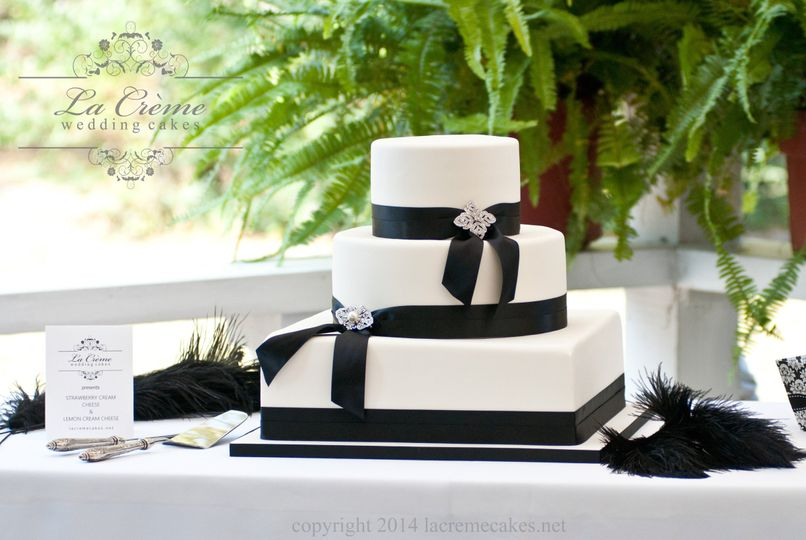 A simple black and white wedding cake adorned with beautiful brooches.