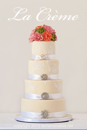 Handmade sugar flowers top this four tier wedding cake covered in pale cream fondant and piped sugar...