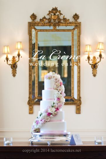 This elegant five tier wedding cake is accented with a beautiful fresh flower cascade and soft pink...