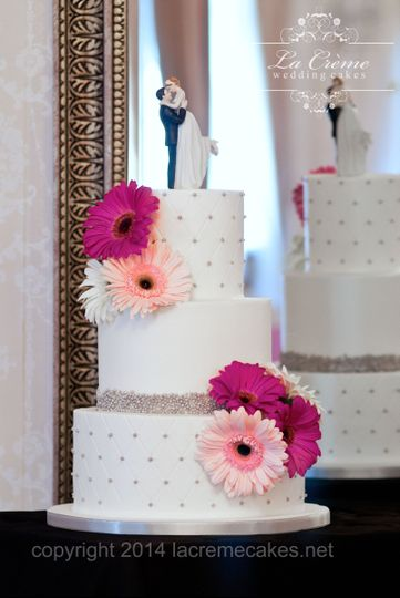 Gerbera daisies add whimsy to this cute three tier buttercream wedding cake with edible silver...