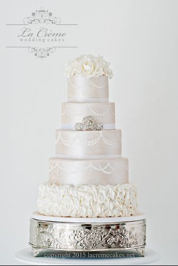 An elegant five tier wedding cake for over 200 guests with pearlized fondant, handmade sugar roses,...