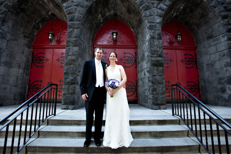 Couple stands beside Trinity's doors