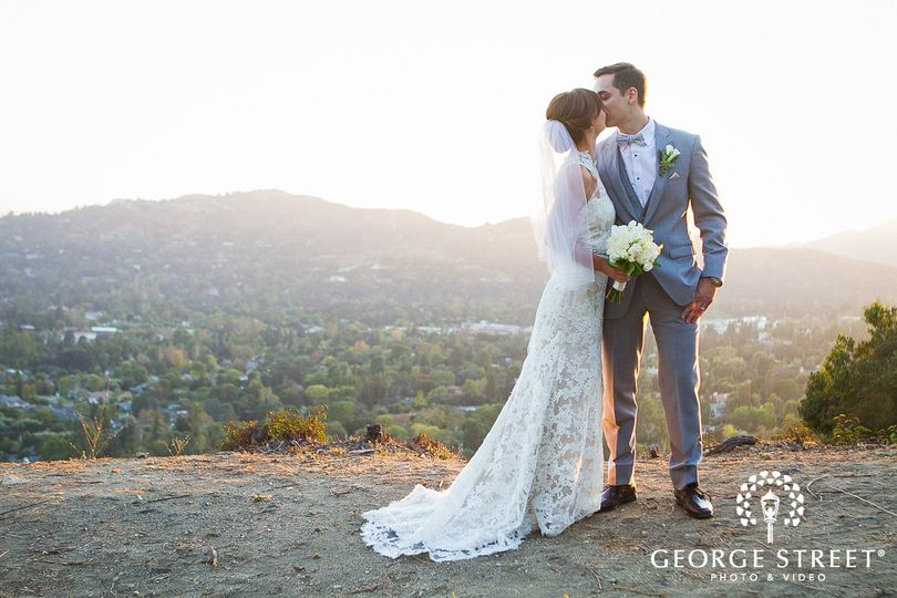 bride and groom kissing during golden hour on a hilltop 51 40791 158344736448002