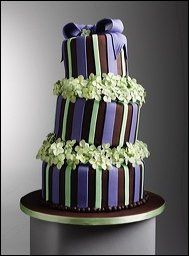 A whimsical crooked cake covered in chocolate fondant with handmade sugar hydrangeas between each...