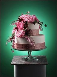 A fondant cake elegantly decorated with handmade sugar peonies, bleeding hearts, and red maple...