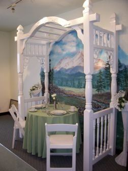Garden style arbor shown with 3' round table,  white resin chairs, and Celadon linen.
