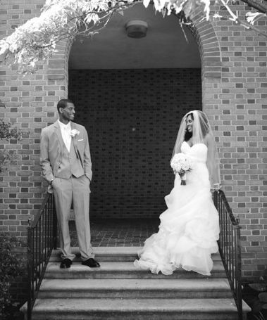 Newlyweds pose by the stairs