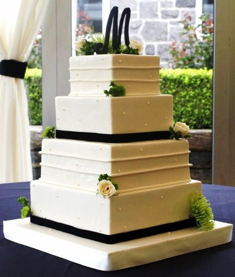 Square, four-tier fondant-covered cake with horizontal lines and pearls.