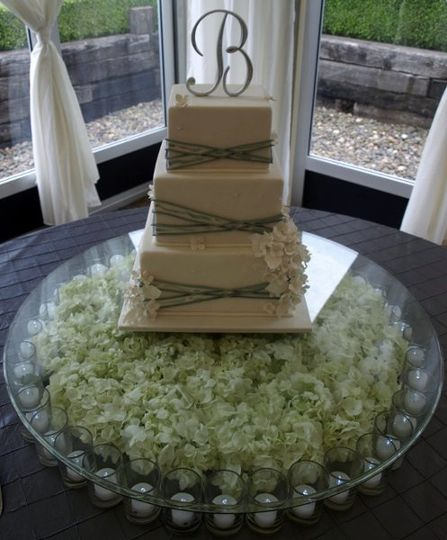 Silver ribbon and gumpaste hydrangea cake, displayed on elevated glass tabletop over candles and...