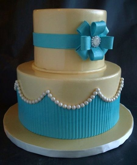 Two tier fondant covered cake with pearls, vibrant blue wrap