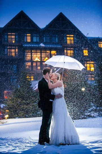 Newlyweds kissing under the snow