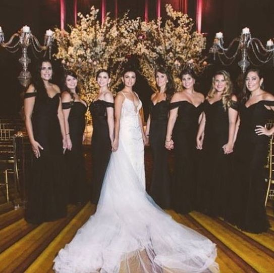 Bridesmaids wearing an off the shoulder dress by Portia and Scarlett in black. Form fitting with a...