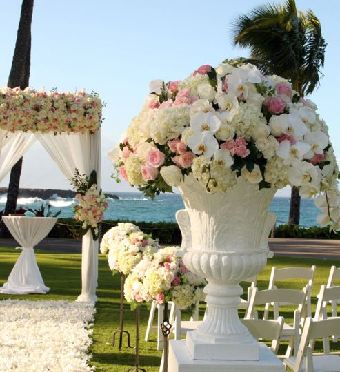 Urns on pedestal overflow with pink and white flowers