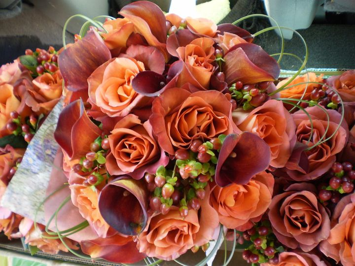 Orange and rust roses, rust mini callas, hypericum berries with bear grass accents