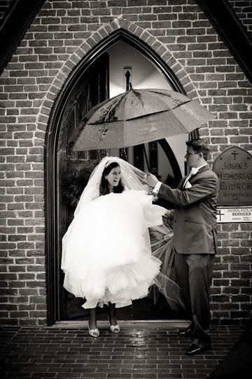 Groom escorting his bride with an umbrella