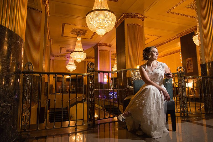 Hilton Milwaukee wedding photographer bride pose in hotel lobby with crystal chandeliers.