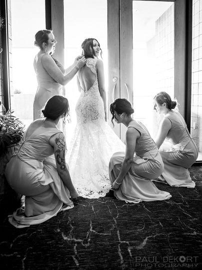 Bridesmaids preparing bride