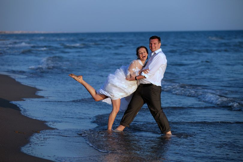 A playful couple having fun at their informal Italian beach wedding!