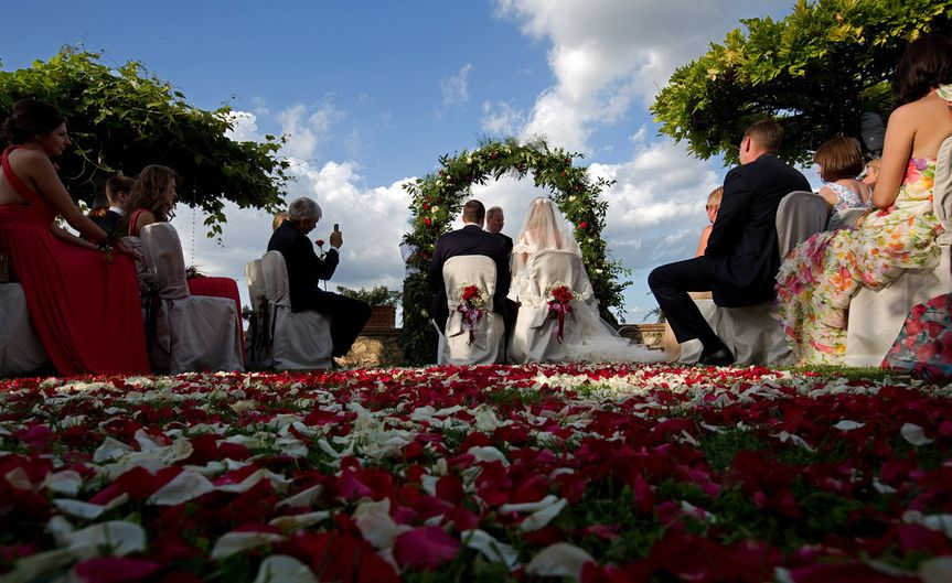 Scattered rose petals about add a romantic flair to this romantic outdoor ceremony.