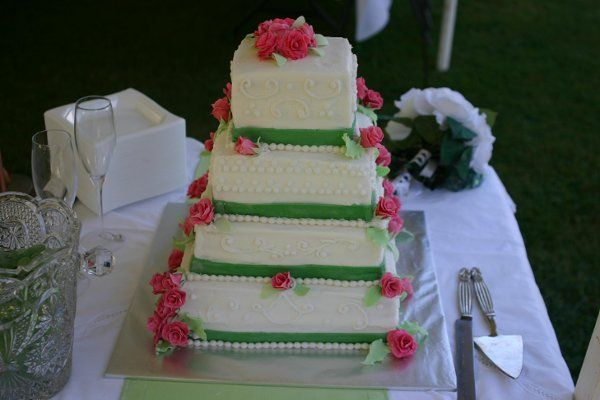 4 tier butter cake with butter cream icing and fondant ribbons and gumpaste roses.