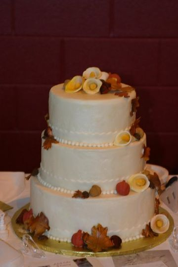 3 tier fondant covered ivory cake with gumpaste cali lilies, pumpkins, and leaves.