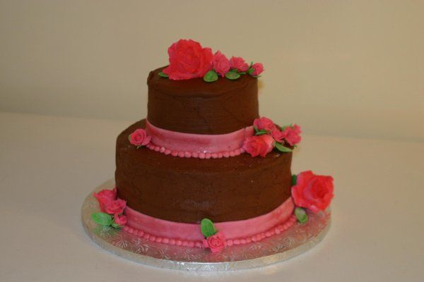 2 tier chocolate cake with chocolate buttercream with gumpaste roses and fondant ribbons and pearls.