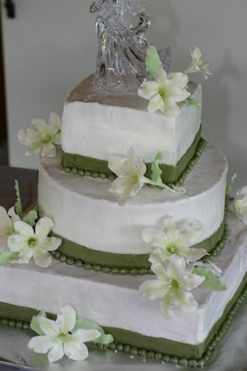 Multi shaped 3 tier white cake with lilies and green fondant ribbons and pearls.