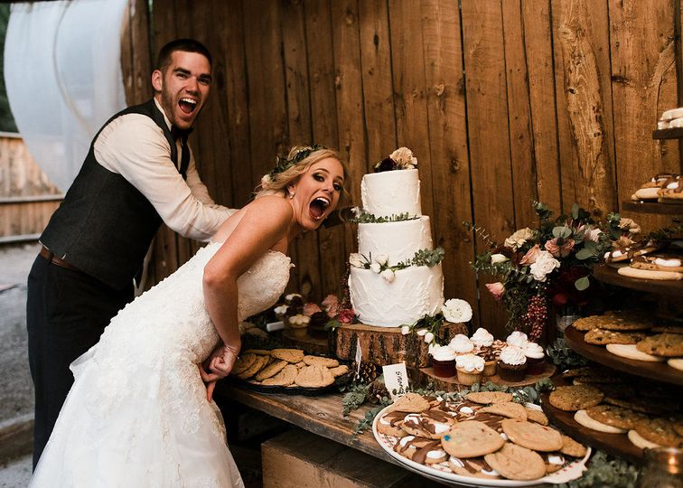 Newlyweds by their cake | Photo Credits: Kate Salley Photography