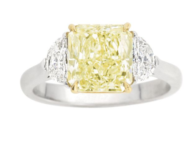 A stunning Radiant cut Fancy Yellow Diamond is accented by two colorless half-moon diamonds, set...