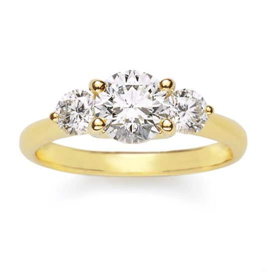 Always a classic, this 18K yellow gold ring cradles three colorless round brilliant diamonds, for...