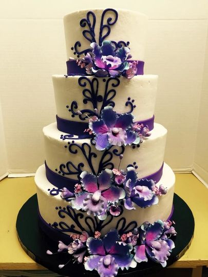 Dark purple cymbidium orchid gum paste flowers on a buttercream iced cake