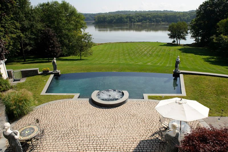 Vanishing edge spa and pool above lawn and Hudson River