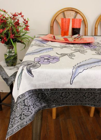 Floral hand painted patterns adorn this unique square tablecloth