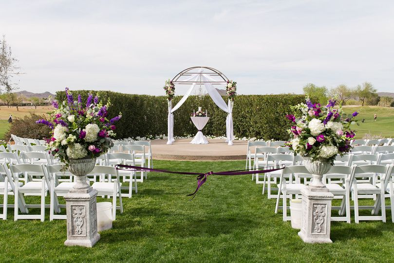 Elegant white chairs and draped altar