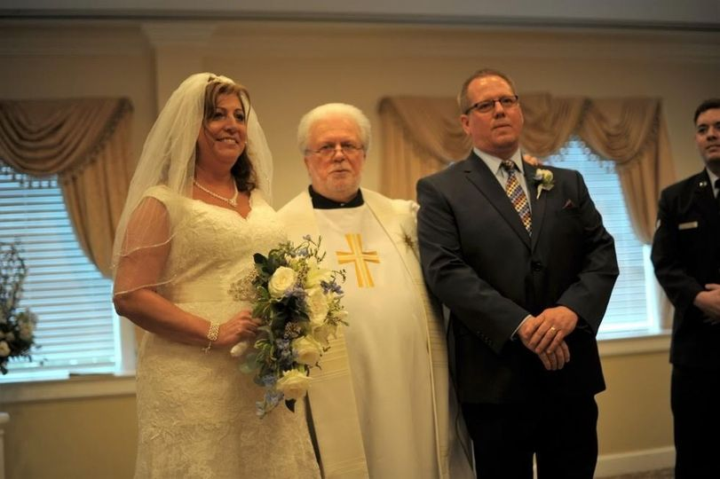 The newlyweds with the wedding officiant