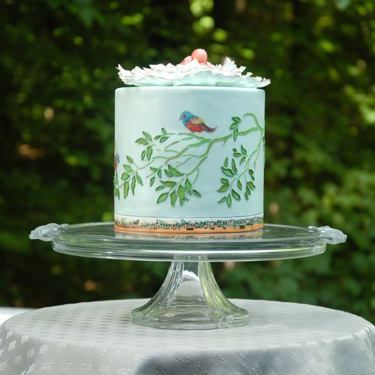 This cake is decorated with a beautiful stenciled branch and two hand painted birds. The top...