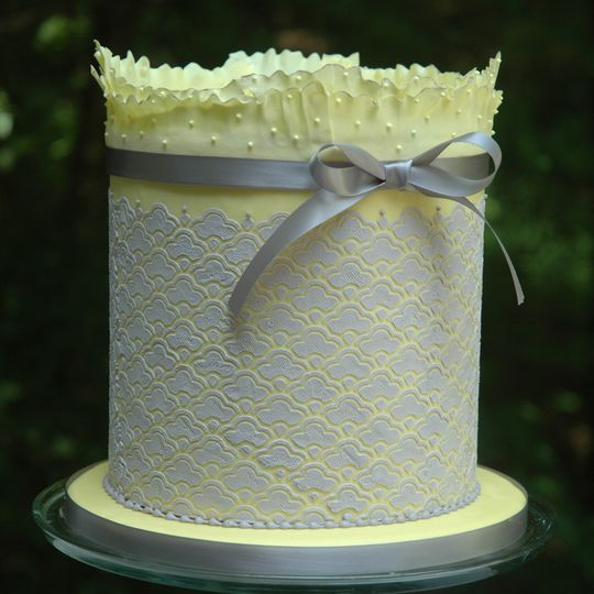 This cake showcases a dense scalloped pattern all around, and a two-layer ruffled top. The ruffles...