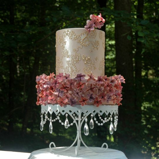 This cake showcases a clean lace design, and some delicate, colorful blossoms and hypericums.