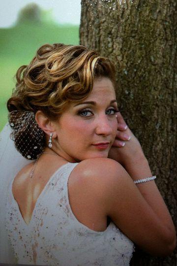 Bride posing by a tree