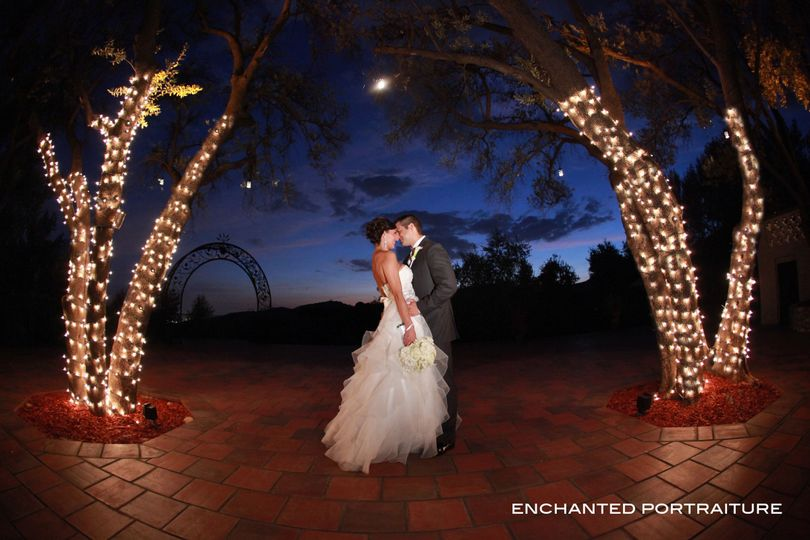 Bride and groom kissing among the magical lights
