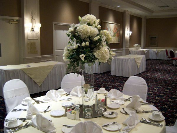 Tall centerpieces add drama and height to an intimate reception, complete with white chairs covers...