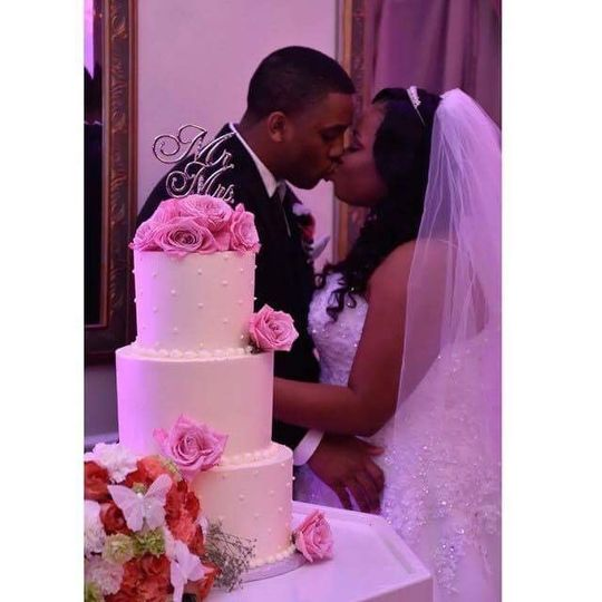 Kissing by the wedding cake